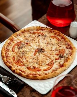 Pizza margarita gegarneerd met plakje tomaat en gedroogde muntblaadjes