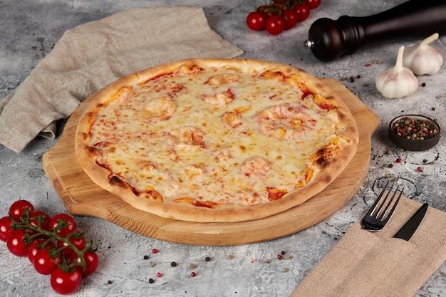Pizza margarita, houten plank, grijze achtergrond