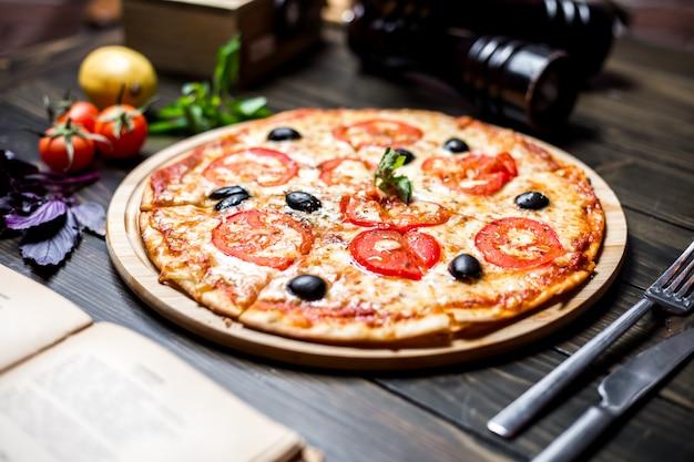 Pizza margarita met tomaten zijaanzicht