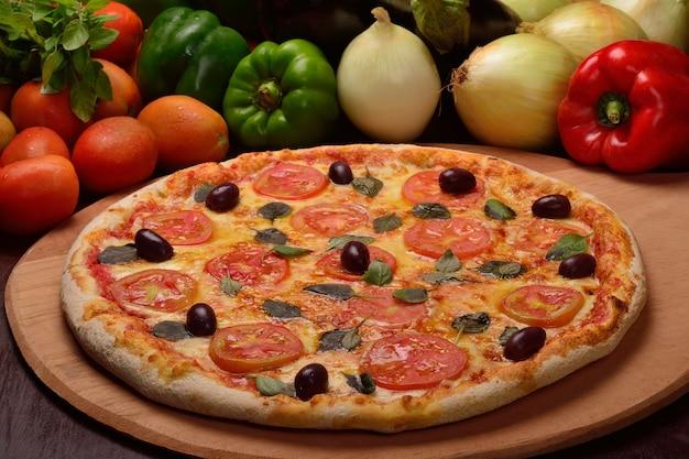 Pizza margherita met zwarte olijven op een houten bord en groenten op de achtergrond.