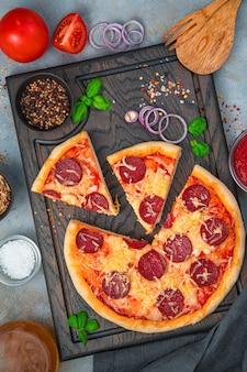 Pizza met basilicum, kaas en salami op een snijplank op een grijze achtergrond. snel voedselconcept. verticale weergave.