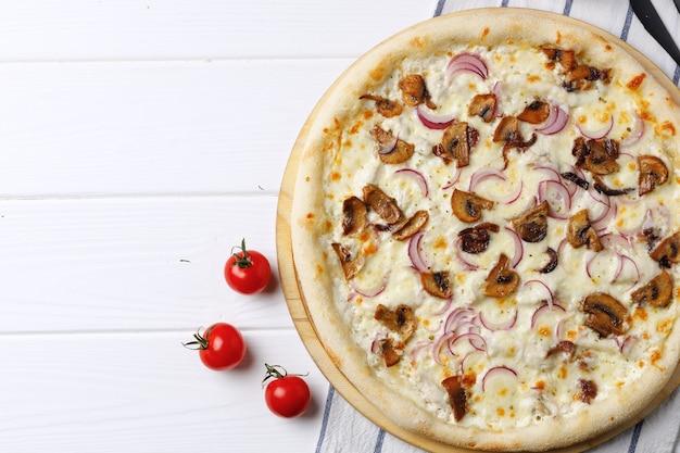 Pizza met champignons en ui aan boord op witte houten tafel close-up