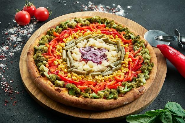 Pizza met een groot aantal toppings: asperges, paprika, ui, mais, broccoli en kaas. pizza in samenstelling met ingrediënten op een zwarte tafel. vegetarisch eten