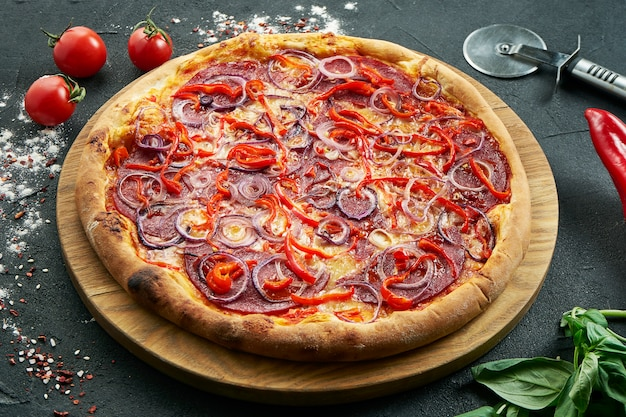 Pizza met een groot aantal toppings: jachtworsten, uien, salami, kaas en chili. pizza in samenstelling met ingrediënten op een zwarte tafel
