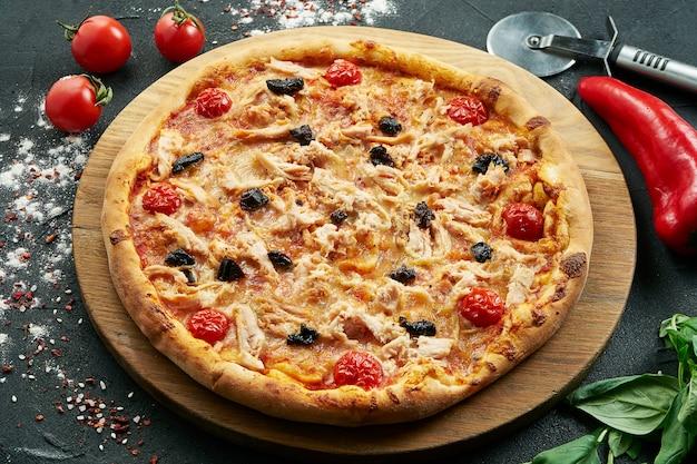 Pizza met een groot aantal toppings: kip, uien, champignons, kaas en roomsaus. pizza in samenstelling met ingrediënten op een zwarte tafel
