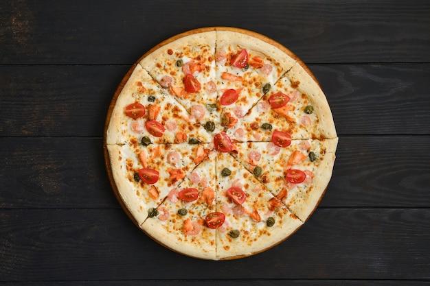 Pizza met garnalen, zalm, tomaat en kappertjes op houten tafel