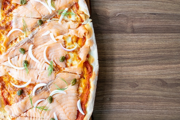 Pizza met gerookte zalm op houten bord