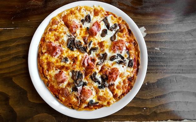 Pizza met ham en champignons, bovenaanzicht.