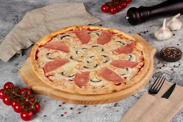 Pizza met ham en champignons, houten plank, grijze achtergrond