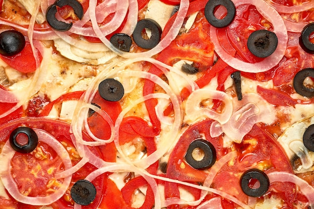 Pizza met ham en tomaten, olijven, saus en gesmolten kaas, knapperige kanten, geïsoleerd op een witte achtergrond