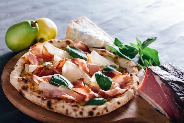 Pizza met ham, peer, basilicum en blauwe kaas