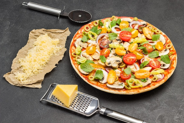 Pizza met ingrediënten is klaar om te bakken. kaasrasp op tafel. geraspte kaas op papier. snijder voor pizza. zwart oppervlak. bovenaanzicht