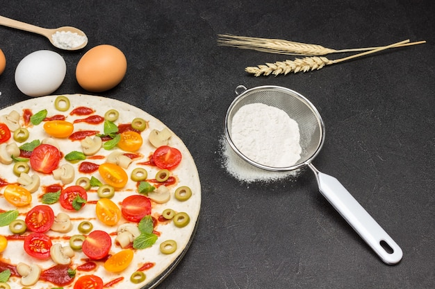 Pizza met ingrediënten is klaar om te bakken