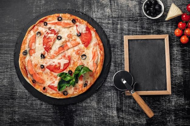 Pizza met kaas, forel, tomaten, olijven en garnalen op schoolbord.
