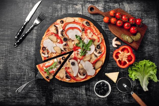 Pizza met kaas, ham, ingelegde komkommers, vlees en olijven op krijtbord.