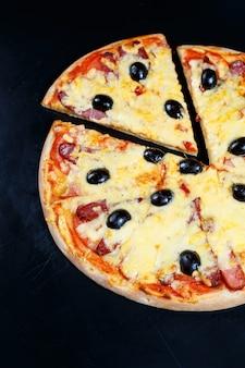 Pizza met kaas-tomatensaus, olijven, verse mozzarella, parmezaan en basilicum en vlees op een donkere ondergrond