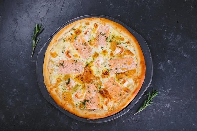 Pizza met kaaspeper en tomaten op hout