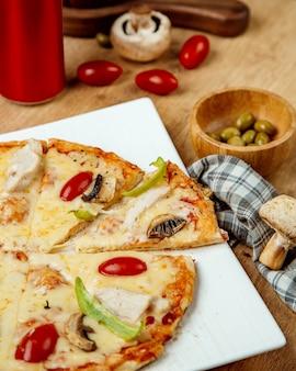 Pizza met kip champignons en tomaten