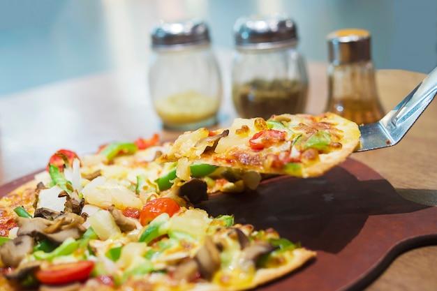Pizza met kleurrijk plantaardig bovenste laagje klaar om worden gegeten