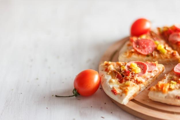 Pizza met maïs, worst, tomaten op een houten ronde bord