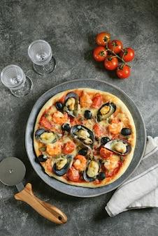 Pizza met mosselen in schelpen, garnalenstaarten, kappertjes en olijven