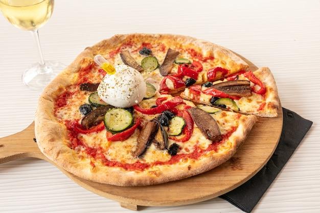Pizza met mozzarella en groente geserveerd op een bord