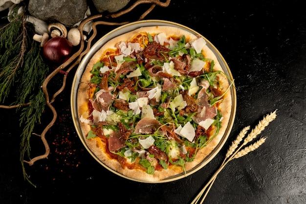 Pizza met parmaham, parmezaanse kaas, gedroogde tomaten en rucola