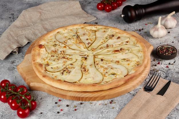 Pizza met peer en gorgonzola kaas op houten bord, grijze achtergrond