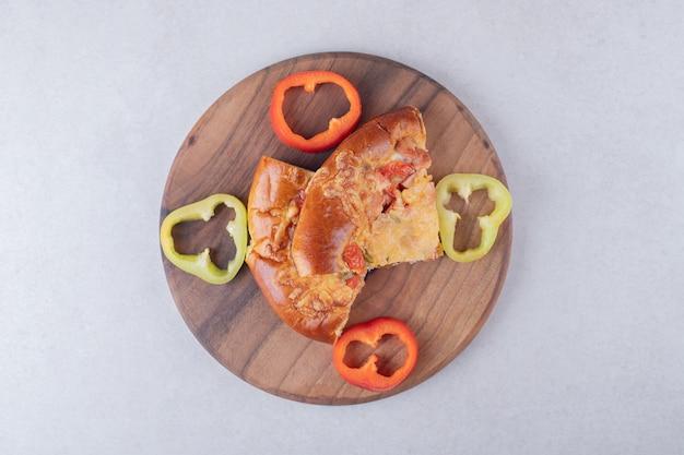 Pizza met peper aan boord op marmeren tafel.