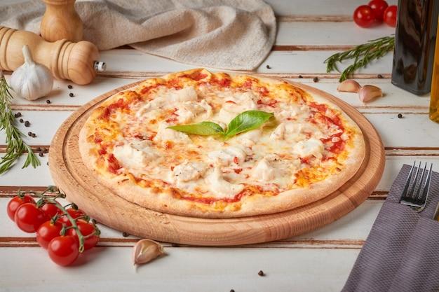 Pizza met plakjes, saus en kruiden, houten wit