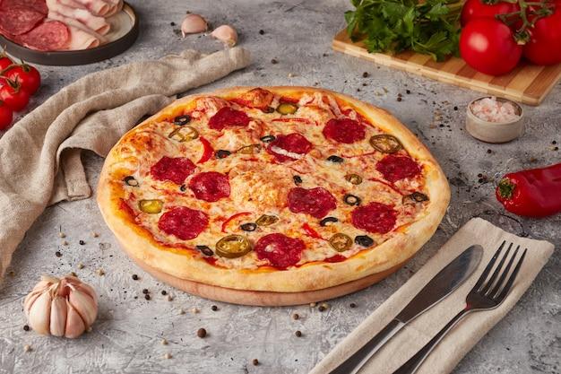 Pizza met plakjes, saus en kruiden