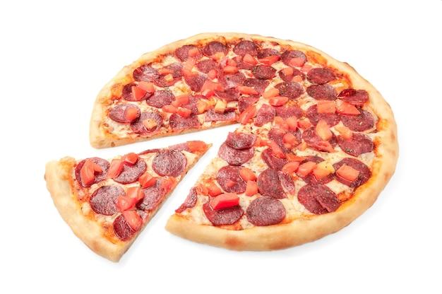 Pizza met plakjes tomaat, pepperoni, ingelegde komkommers, mozzarella kaas, groen. uien, oregano. van pizza wordt een stuk afgesneden. witte achtergrond. geïsoleerd. detailopname.