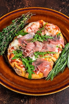 Pizza met prosciutto parmaham, rucola salade en parmezaanse kaas in een rustieke plaat. houten achtergrond. bovenaanzicht.