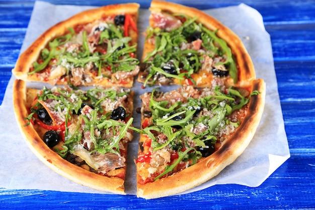 Pizza met rucola op houten kleur