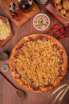 Pizza met rundvlees en room, mozzarellakaas en aardappelsticks