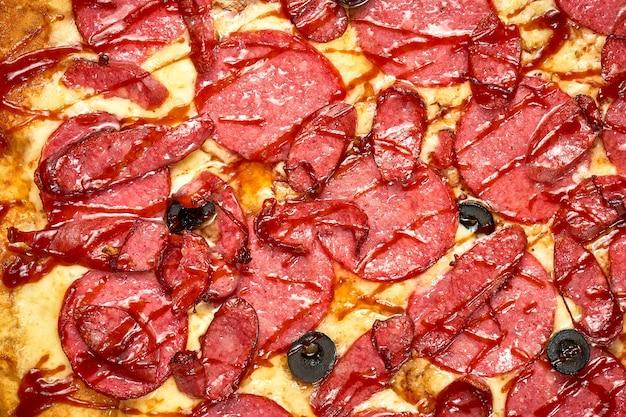 Pizza met salami en rookworst, saus en gesmolten kaas, krokante zijkanten, geïsoleerd op een witte achtergrond