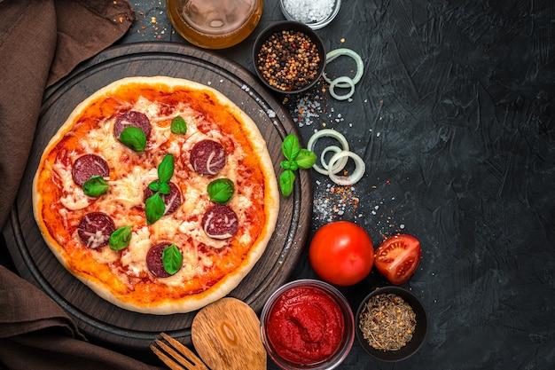 Pizza met salami, tomaten en kaas op een zwarte achtergrond.