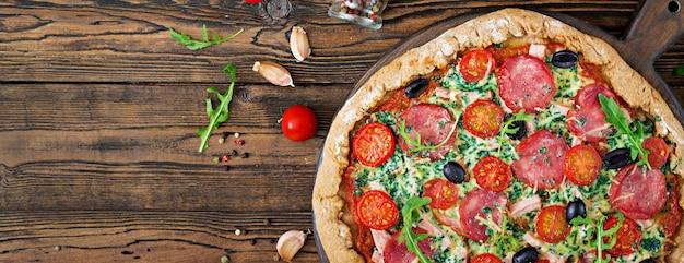 Pizza met salami, tomaten, olijven en kaas op een deeg met volkoren meel. italiaans eten. bovenaanzicht plat leggen.