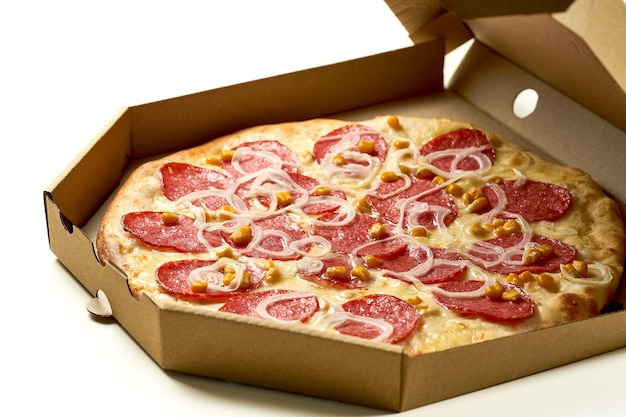 Pizza met salami, ui en maïs, saus en gesmolten kaas, knapperige zijkanten, geïsoleerd op een witte achtergrond