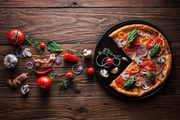 Pizza met spek en ham zonder één plak op een leisteen zwarte schotel die op houten achtergrond, bovenaanzicht en kopie ruimte is