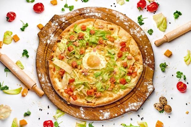 Pizza met spekvlees, eigeel en groene salade op de houten plaat