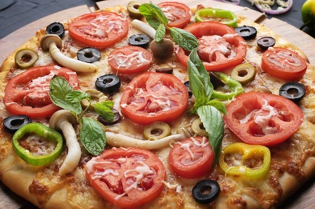 Pizza met tomaat, olijven en champignons. italiaanse keuken. ingrediënten voor het maken van pizza. professioneel product.bovenaanzicht.concept voor het adverteren van restaurants of pizzeria's.