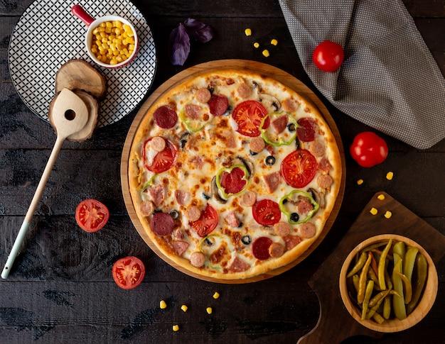 Pizza met tomaat plakjes en pepperoni.