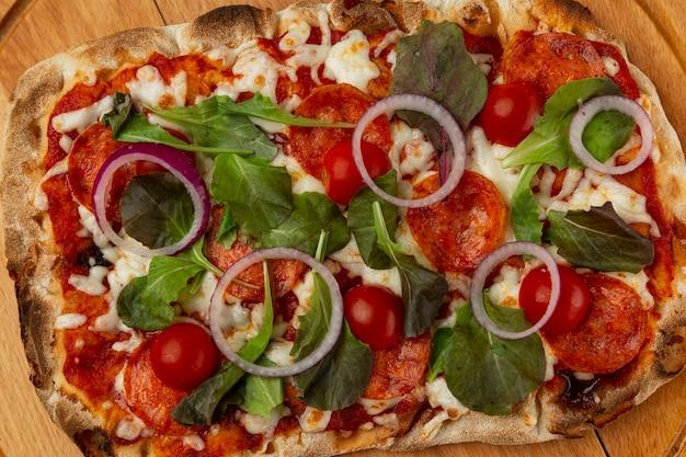 Pizza met tomaten en kaas op een houten bord. een smakelijk traditioneel tussendoortje. detailopname.