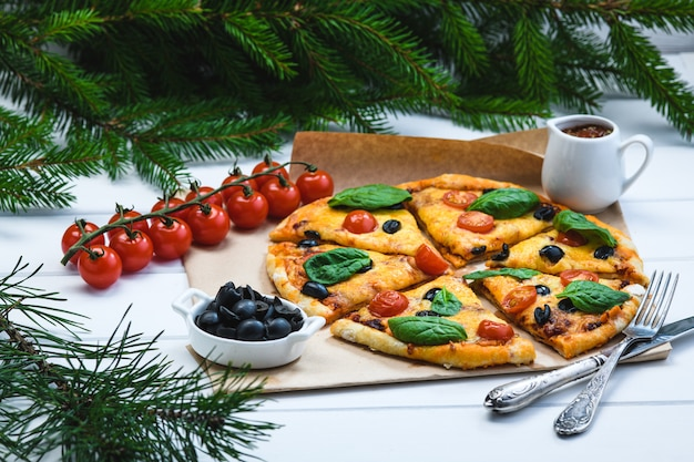 Pizza met tomaten en spinazie op een witte achtergrond en kerstmisspartakken
