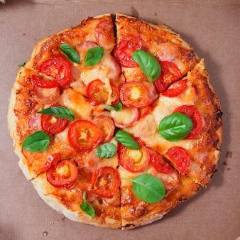 Pizza met tomaten, worstjes en kaas in een kartonnen doos