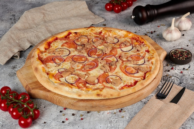 Pizza met tonijn op een houten bord, grijze achtergrond