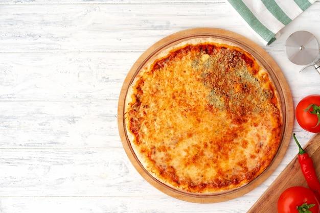 Pizza met vier kazen geserveerd op houten achtergrond bovenaanzicht