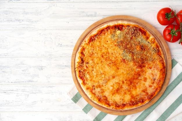 Pizza met vier kazen geserveerd op houten oppervlak