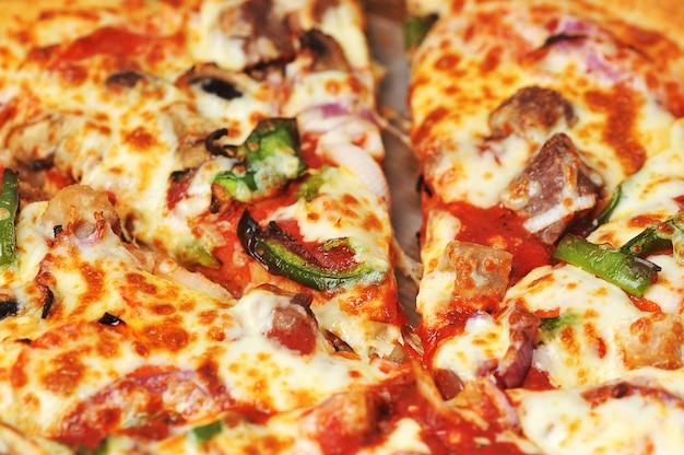 Pizza met vlees en peper ligt op karton